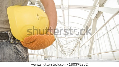 torso and hand in gloves manual worker holding yellow helmet for workers security on metal and glass air above the urban pedestrian crossing highway background