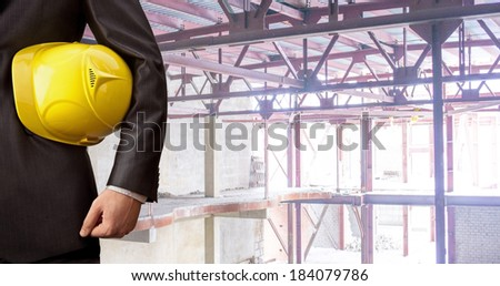 torso engineer hand holding yellow helmet for workers security against the support metal beams of the unfinished industrial concrete workshop or room inside Copy space for inscription #184079786