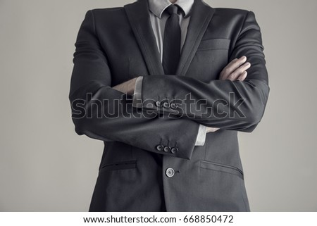 Torso of a businessman standing with folded arms in a classic black suit, vintage effect toned image.