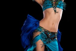 Torso of a female belly dancer wearing a teal blue costume and shaking her hips. Isolated on a black background.