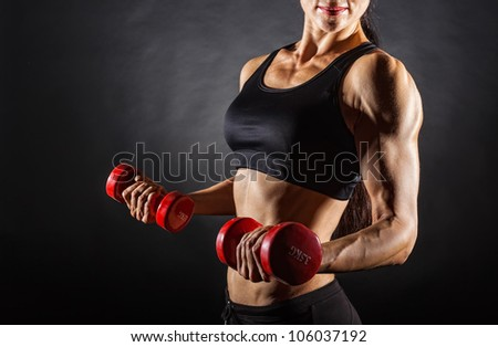 Torso of a young fit woman lifting dumbbells on dark background