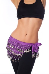 Torso of an athletic female belly dancer wearing a lavender colored coin belt, black sports bra and leggings. Isolated on white.