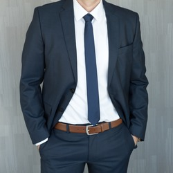 Torso of anonymous white collar worker standing with hands in pockets, wearing beautiful fashionable classic navy blue suit against grey backgound.