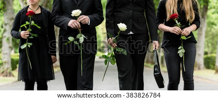 Torso of family on cemetery mourning holding red and white roses in hands