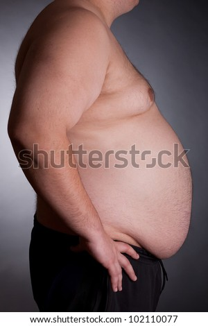 Torso of fat man on dark background