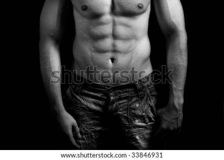 Torso of muscular man with nice abdomen over black