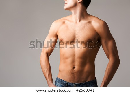 Torso of shirtless man in jeans posing in front of camera