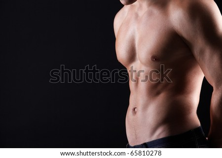 Torso of strong man in jeans against dark background