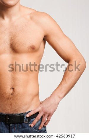 Torso of strong man in jeans with his arm on hip