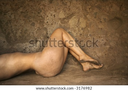 stock photo : Torso of young nude woman lying in a cave with bent legs.