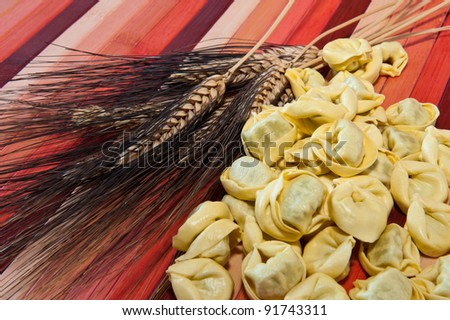 Tortellini and ears of wheat colored bamboo background