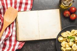Tortellini pasta and blank cookbook. Italian stuffed pasta. Top view.