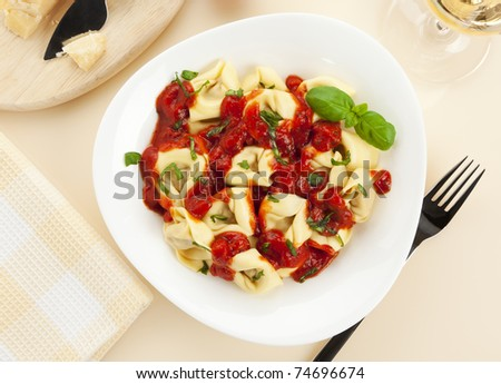 tortellini pasta with tomato sauce on a plate, high angle view