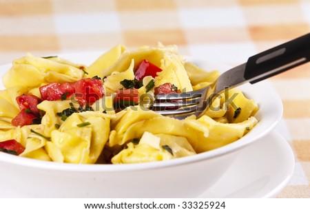 Tortellini primavera garnished with basil leaves on white plate