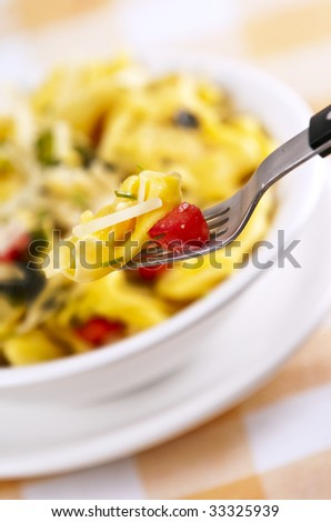 Tortellini primavera garnished with basil leaves on white plate