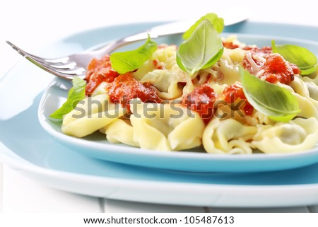 Tortellini with tomato sauce and cheese, fresh basil