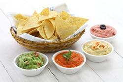 tortilla chips with four super bowl dips which are salsa roja, guacamole, taramasalata, and hummus.