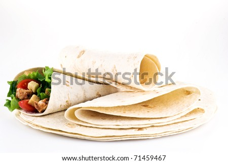 Tortilla filled with lettuce chicken tomatoes and cucumber with plain tortillas