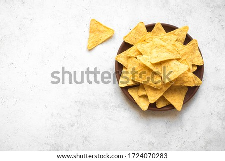 Tortilla or Nacho Chips for snack. Mexican Corn Chips Nachos on white background, top view, copy space.