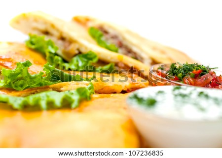 Tortilla stuffed with meat sliced ??and decorated with lettuce leaves with a cream sauce. A series of food in a restaurant close-up