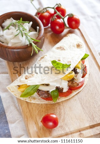 tortilla with chicken meat, fries and basil