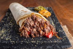Tortilla with pulled beef meat, onion and tomato serving on black plate with humus and jalapeno pepper.