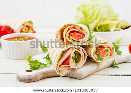 Tortilla wrap with ham, cheese and tomatoes on a white wooden background