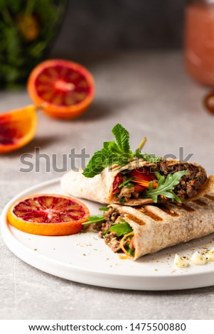 Tortilla wraps sandwiches with fresh vegetables, minced meat and blood oranges on plate. Burrito, sandwich wrap, fajita wrap