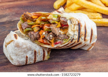 Tortilla wraps sandwiches with fresh vegetables, minced meat and served with french fries on cutting board. Burrito, sandwich wrap, fajita wrap.