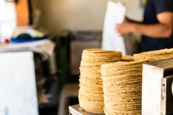 tortillas stacked on a tortilla machine in typical mexican shop