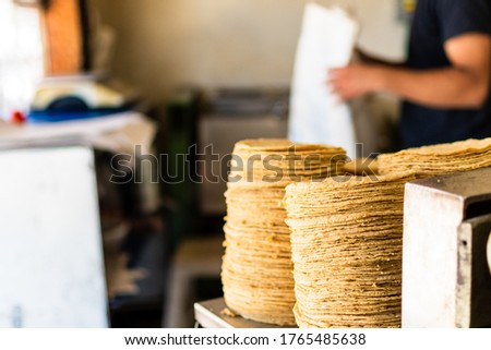 Photo of  tortillas stacked on a tortilla machine in typical mexican shop