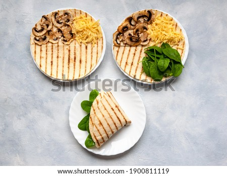 Photo of  Tortillas with different fillings of mushrooms, cheese, spinach and fried egg. Food trend.
