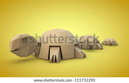 tortoises origami made with cardboard paper isolated on yellow background