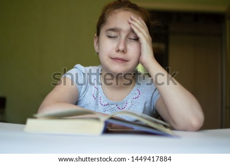 tortured girl child reads a book at the table and she is very tired and wants to sleep, yawns, falls asleep while reading stories and lessons