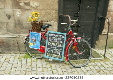 TORUN, POLAND - OCTOBER 23, 2014: bicycle on the street with an advertising poster