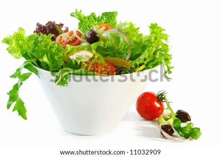 Tossed green salad in a white bowl.  Mixed greens with black olives, cherry tomatoes, goat's cheese, bell pepper and red onion.