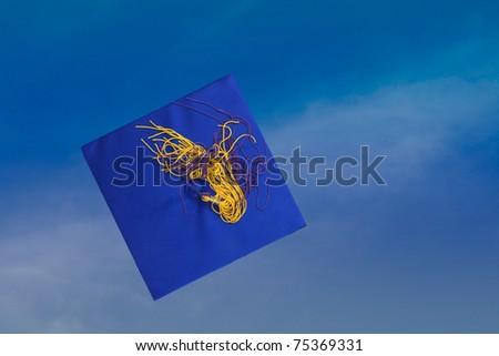 Tossed Up Graduation Hat on Blue Sky Background