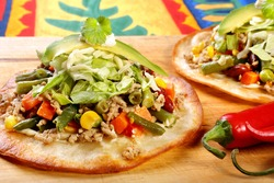 Tostadas with ground beef and vegetables on wooden background