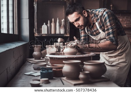 Total concentration at work. Confident young man making ceramic pot on the pottery wheel