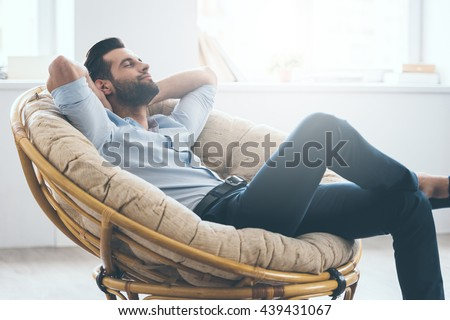 Total relaxation. Handsome young man keeping eyes closed and holding hands behind head while sitting in big comfortable chair at home   #439431067
