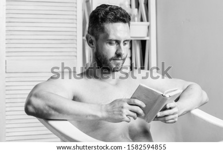 Total relaxation. Personal hygiene. Nervous system benefit bathing. Relax concept. Man muscular torso relax bathtub and read book. Relaxed guy reading book while relaxing in hot bath. Relax at home.