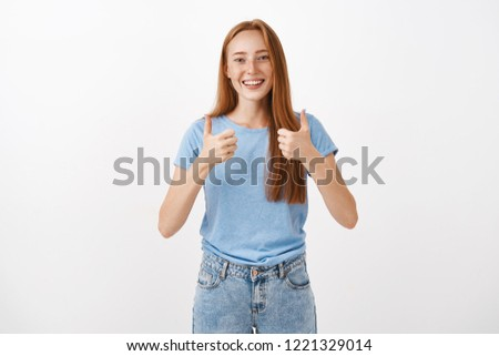 Totally agree and support you. Portrait of joyful pleased good-looking redhead female with freckles showing thumbs up and smiling supportive and cheering giving positive answer over gray background