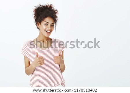 Totally agree with your opinion. Satisfied happy and outgoing woman with dark skin in striped t-shirt, raising thumbs up and smiling broadly, giving approval and liking interesting idea of friend