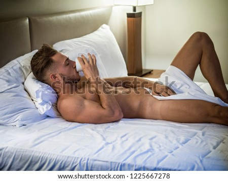 Totally naked sexy young man with muscular body on bed with mug or cup in hand with coffee or tea