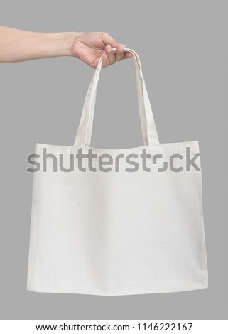 Tote bag canvas white cotton fabric cloth eco shopping sack mockup blank template isolated on grey background (clipping path) with woman's handling hand