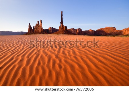 Totem pole and sand dunes in morning light at Monument Valley - stock photo