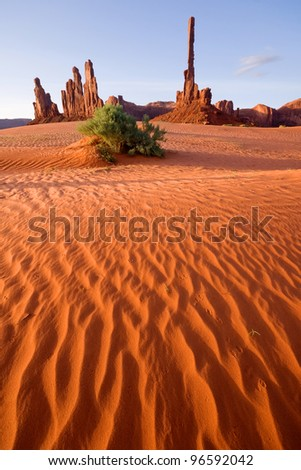 Totem pole and sand dunes in morning light at Monument Valley