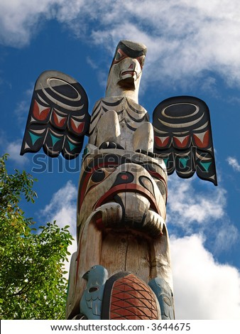 Totem pole carved in wood with sky background