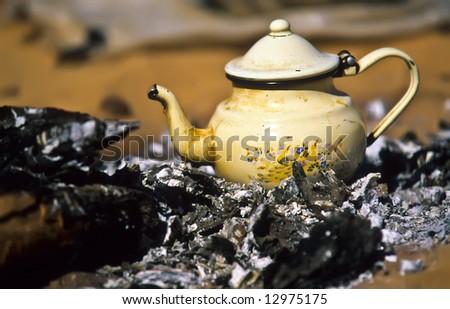 Touareg teapot on live coal in a camp