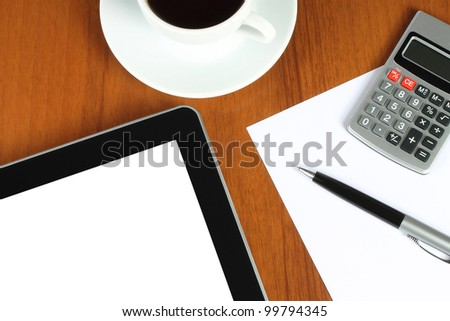 Touch screen device and stationery with cup of coffee on wooden background